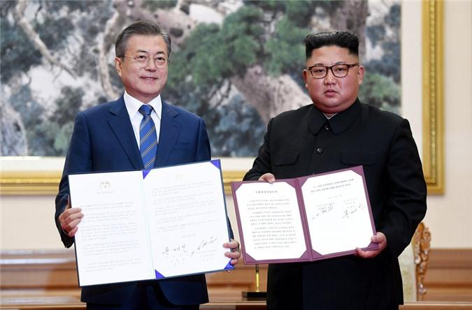 Nhà lãnh đạo Kim Jong-un và Tổng thống Moon Jae-in trưng tuyên bố chung vừa ký kết. (Ảnh: Reuters)