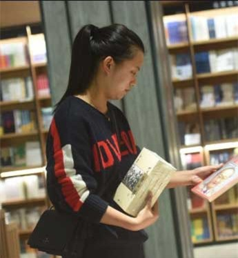 Một bạn đọc tham khảo mua sách của Kim Dung. Ảnh: GETTY/AFP