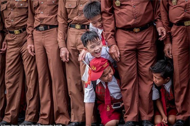 """Donny Herry đến từ Indonesia chụp những em học sinh tiểu học đang hiếu kỳ chen vào hàng của những cựu quân nhân tại một sự kiện dành cho các quân nhân. Nhiếp ảnh gia tâm niệm: """"Học từ lịch sử để có tương lai tốt đẹp hơn. Trẻ em là hy vọng của mỗi đất nước""""."""