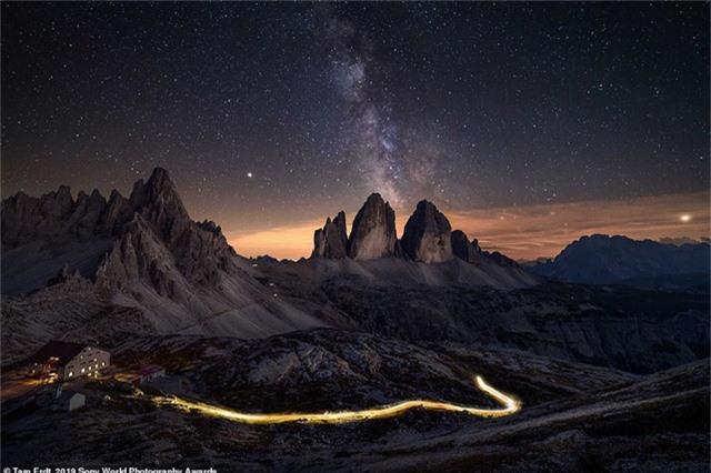 Tam Erdt đến từ nước Đức chụp bức ảnh này ở núi Tre Cime di Lavaredo, miền đông bắc nước Ý, với mong muốn chụp được dải Ngân hà. Bất ngờ, một chiếc xe hơi chạy qua và tạo nên một dải ảnh sáng trên con đường núi trong bức ảnh chụp phơi sáng.