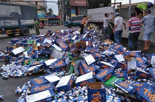Người dân Bình Thuận giúp tài xế gom hàng trăm thùng bia đổ ra đường