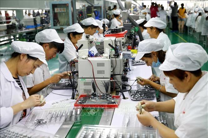 Công nhân làm việc trên dây chuyền sản xuất động cơ siêu nhỏ tại nhà máy ở Hoài Bắc, An Huy, Trung Quốc. (Ảnh: AFP/TTXVN)