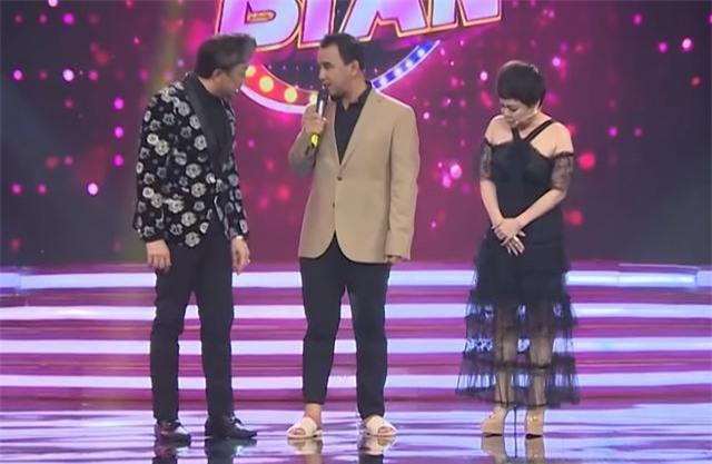 Quyền Linh mặc vest, đi dép tổ ong dẫn chương trình Ca sĩ bí ẩn.