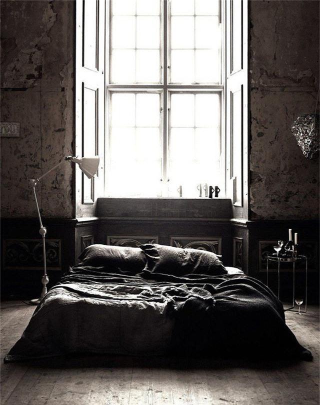 Một chiếc giường đặt cạnh một khung cửa sổ kính cỡ lớn khiến nó trông thật cá tính.