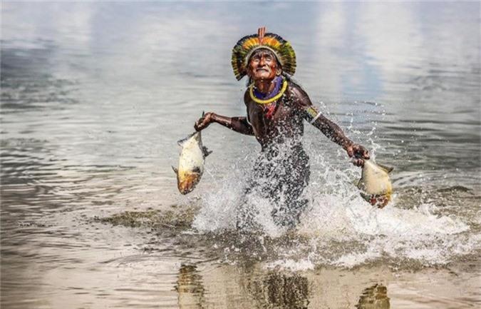 Một người đàn ông bộ lạc Bejà Kayapó tìm đường qua sông Xingu với một con cá trong tay sau chuyến săn bắt thành công.