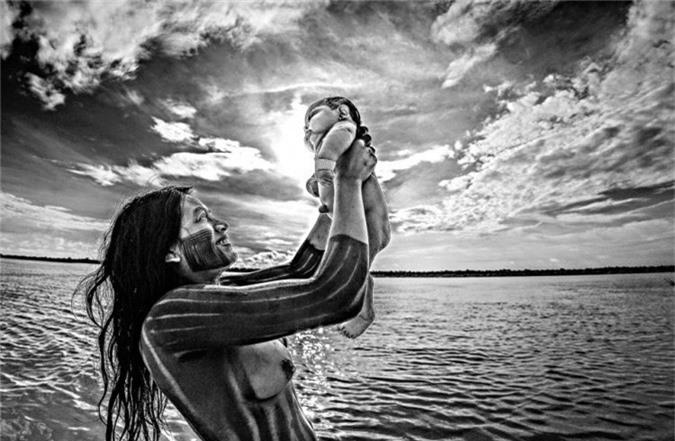 Người phụ nữ bộ lạc Kayapó tắm cho em bé ở sông Xingu, bang Mato Grosso.