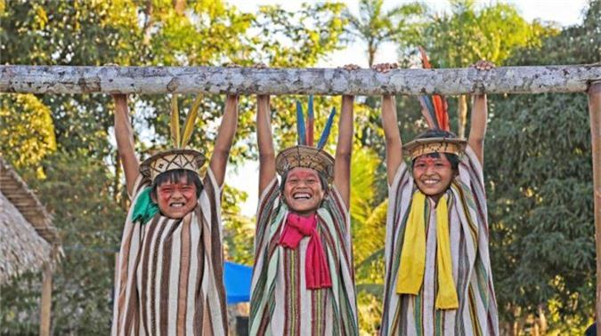 """Những đứa trẻ Ashaninka tươi cười khi cùng chơi đùa trên một thanh gỗ ngang ở làng Apiwtxa. Theo nhiếp ảnh giaRicardo, thổ dân da đỏlà người đầu tiên sống ở Brazil. """"Chúng ta nợ họ một phần quan trọng trong mọi khía cạnh của văn hóa.Họ là những chiến binh vẫn chiến đấu chống lại rất nhiều nghịch cảnh. Họ yêu thiên nhiên và đấu tranh vì thiên nhiên"""".Đó là lý do tại sao Ricardo quyết định xuất bản cuốn sách về người da đỏ Brazil vào năm nay."""