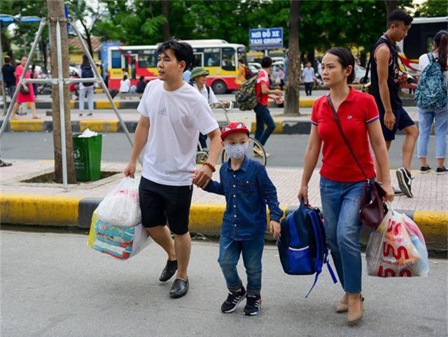 Hình ảnh một gia đình lỉnh kỉnh ba lô, túi xách về quê trong dịp nghỉ lễ kéo dài.