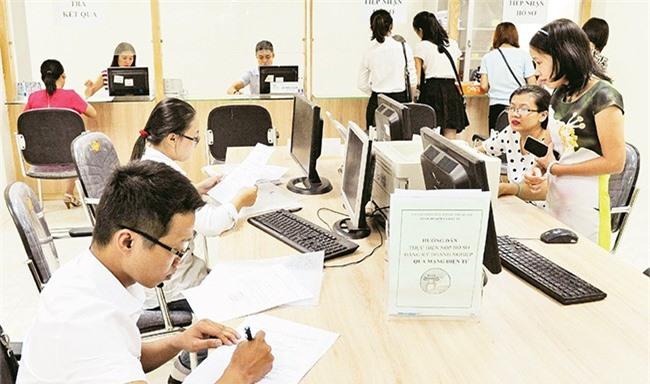 Doanh nghiệp làm thủ tục hành chính tại Bộ phận tiếp nhận hồ sơ và giải quyết thủ tục hành chính (Sở Kế hoạch và Đầu tư Hà Nội). Ảnh: HÀ MINH
