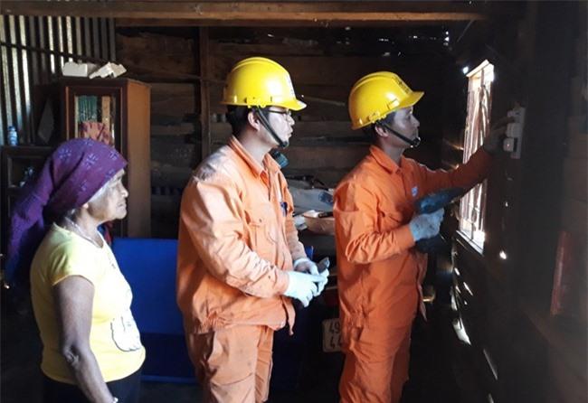 Nhân viên Công ty Điện lực Lâm Đồng kiểm tra và thay bóng đèn miễn phí cho đồng bào dân tộc thiểu số (ảnh VH).