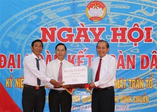 Phó Thủ tướng Trương Hòa Bình trao quà cho cán bộ Khu phố Bình Quới A. Ảnh: VGP/Mạnh Hùng.
