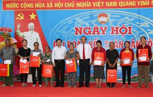 Phó Thủ tướng Trương Hòa Bình trao quà cho các hộ nghèo thuộc Khu phố Bình Quới A. Ảnh: VGP/Mạnh Hùng.