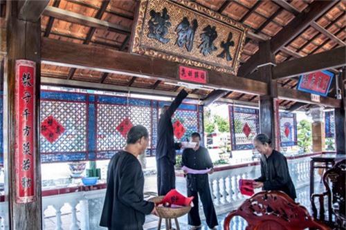 Những vị kỳ lão theo đạo ông Trần dán liễn Tết ở Nhà Lớn Long Sơn. Ảnh: Hoài Ân