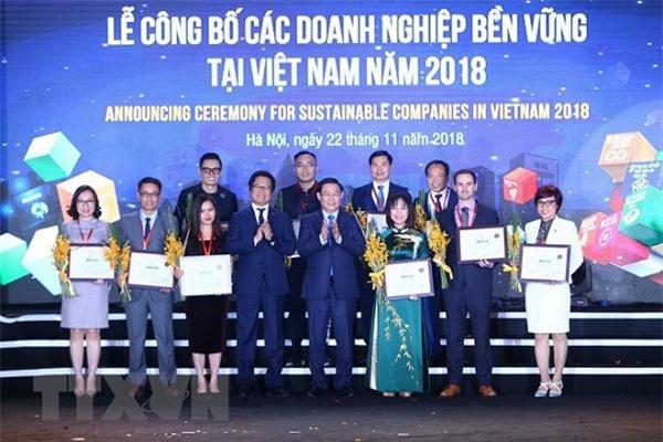 Phó Thủ tướng Chính phủ Vương Đình Huệ và Chủ tịch VCCI Vũ Tiến Lộc trao chứng nhận cho các doanh nghiệp 3 năm liền nằm trong top 10 doanh nghiệp bền vững. (Ảnh: Minh Quyết/TTXVN)