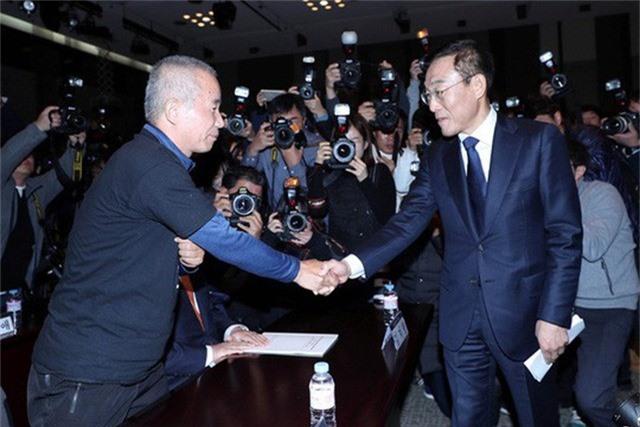 Giám đốc điều hành Samsung Electronics Kim Ki-nam (phải) bắt tay với ông Hwang Sang-gi, người sáng lập nhóm Sharps, tại sự kiện ký thỏa thuận đền bù ở Seoul ngày 23-11. Ảnh: REUTERS