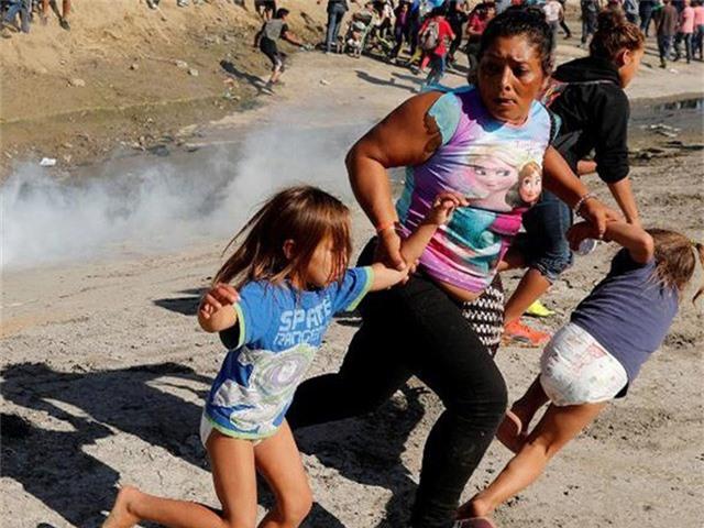 Người mẹ Maria Mesa và hai con nhỏ chạy tránh hơi cay do lực lượng biên phòng Mỹ bắn ra ở khu vực biên giới TP Tijuana (Mexico) và TP San Diego (Mỹ). Ảnh: CNN