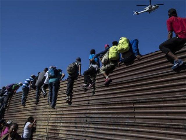 Người di cư leo rào biên giới ngăn Mexico-Mỹ để vào Mỹ. Ảnh: CNN