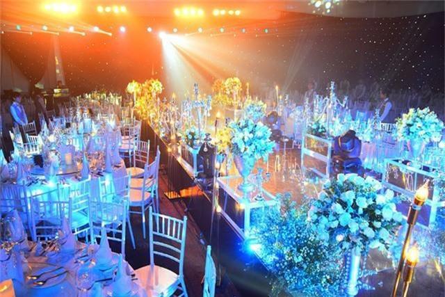 Không gian tiệc cưới được trang hoàng cầu kỳ và lộng lẫy bằng đèn chùm pha lê và hoa tươi với tông trắng chủ đạo và nổi bật.