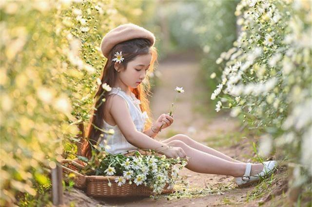 Cô bé giống như một thiên thần trong vườn cúc hoạ mi.