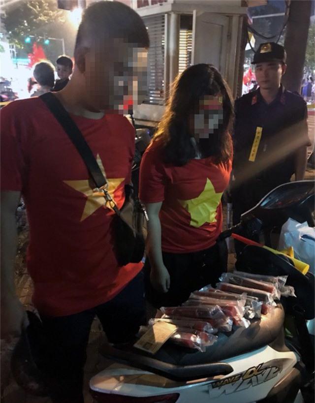 Đôi nam nữ mang pháo sáng đi cổ vũ bóng đá bị cảnh sát chặn dừng.