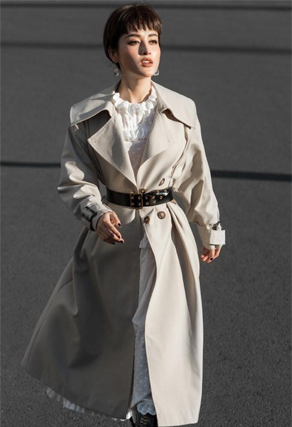 Váy trắng cổ điển phối hợp cùng áo khoác oversize tạo cho Á hậu vẻ ấn tượng.