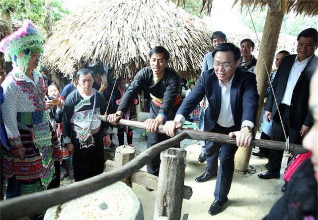 Phó Thủ tướng Vương Đình Huệ cùng bà con dân tộc bản người Mông - Sin Suối Hồ (huyện Phong Thổ, tỉnh Lai Châu) xay ngô - đây là một bản du lịch mới nổi của địa phương này