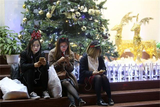 Các cô gái với phụ kiện thời trang Noel bên cạnh một cây thông lớn.