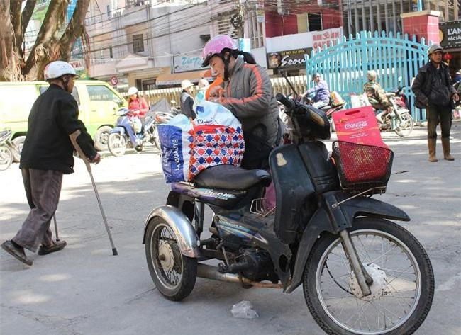 Một cô khuyết tật chăm chút buộc chặt phần quà tết để chở về (Ảnh: VH)