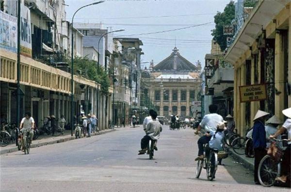 Phố Tràng Tiền vẹn nguyên vẻ đẹp trường tồn cùng thời gian. Phương tiện đi lại chủ yếu của người dân Hà Nội thời bấy giờ là xe đạp, xích lô, xe phân khối nhỏ.