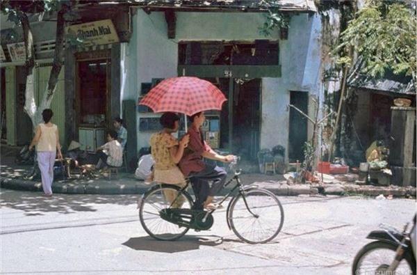 Cảnh lãng mạn điển hình, anh đạp xe Phượng hoàng, em cầm ô Trung Quốc, góc phải có đầu 1 chiếc Honda Dream -