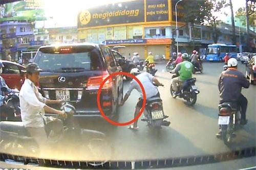 Hình ảnh tên trộm cạy logo chụp mâm của chiếc ô tô hạng sang bị camera ghi lại.