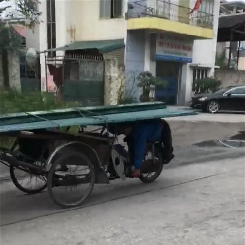 Clip: Người đàn ông nằm úp bụng lên yên, dùng lưng lái xe chở tôn chạy vi vu ngoài đường - Ảnh 2.
