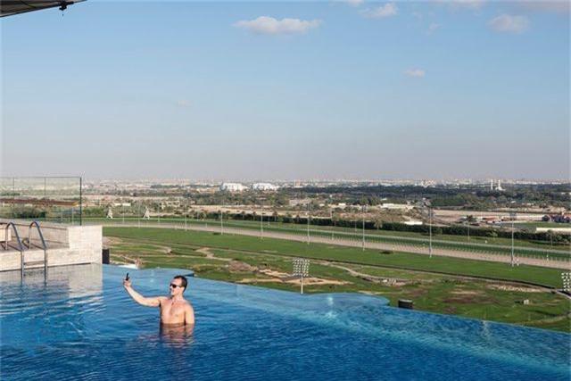 Bể bơi trên tầng thượng hay hồ bơi vô cực nằm tại khách sạn Meydan. Phía sau đó là trường đua ngựa Meydan nổi tiếng, nơi có thể chứa tới 60,000 người xem. Một du khách nam đang thư thái chụp hình trên bể bơi, nơi tầm nhìn hướng về trường đua ngựa.