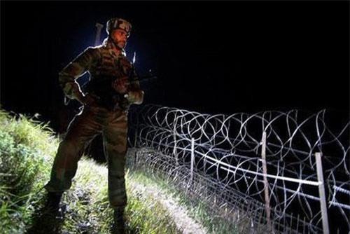 Một binh sỹ Ấn Độ đứng gác cạnh hàng rào thép gai gần Đường kiểm soát (LoC). (Ảnh: AP)