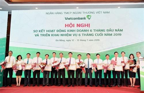 Chủ tịch HĐQT Vietcombank Nghiêm Xuân Thành (thứ 7 từ phải sang) và Tổng giám đốc Phạm Quang Dũng (thứ 6 từ trái sang) trao Giấy khen và tặng hoa cho 14 chi nhánh tiêu biểu trên một số mặt hoạt động 6 tháng đầu năm 2019
