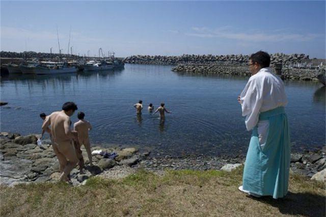 Du khách nam thực hiện nghi lễ tắm misogi để tẩy uế trước khi vào thăm đền thờ