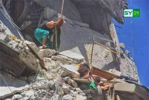 Bức ảnh cho thấy bé gái 5 tuổi đang cố hết sức cứu em gái 7 tháng tuổi không rơi xuống đất (Ảnh: SY24)