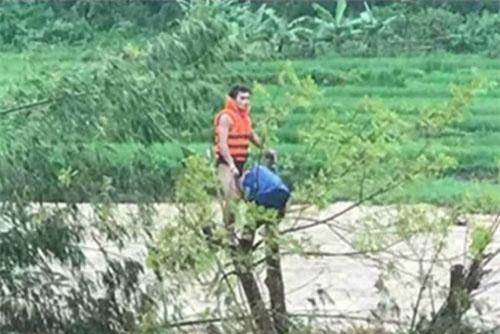 Anh Phạm Bá Huy (người mặc áo phao) quên mình vượt dòng nước lũ cứu người.