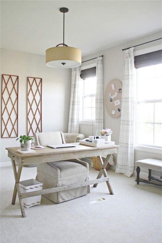 Một phòng làm việc tại nhà có màu trung tính với chất liệu gỗ trắng, nhiều hình in và luồng ánh sáng tự nhiên mạnh chiếu vào từ các cửa sổ.