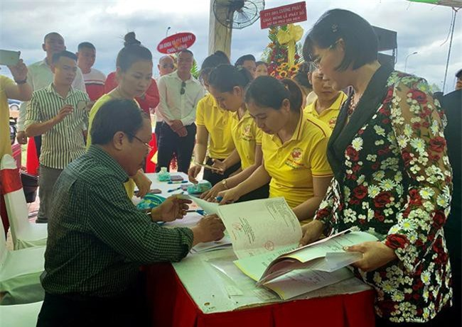 Doanh nhân Phạm Thị Hường (phải) đang chỉ đạo nhân viên lấy sổ đỏ để trao khách hàng (ảnh PHT)