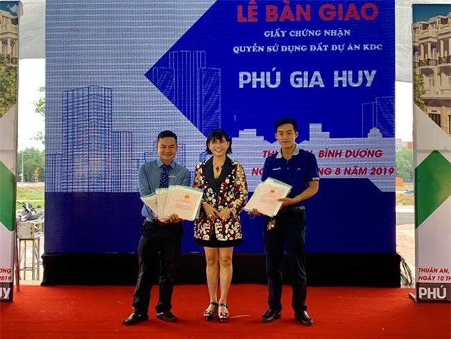 Bà Phạm Thị Hường (giữa), Chủ tịch HĐTV Công ty TNHH Bất động sản Phú Hồng Thịnh, trao sổ đỏ cho 329 khách hàng dự án Phú Gia Huy (ảnh PHT)
