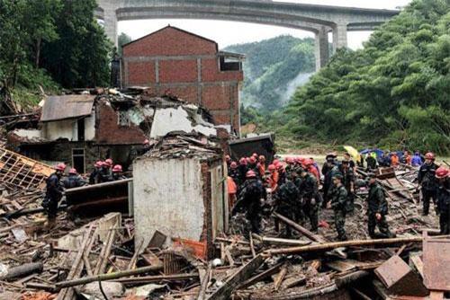 Đội cứu hộ xem xét hiện trường các ngôi nhà bị bão đánh sập (Ảnh: AFP)