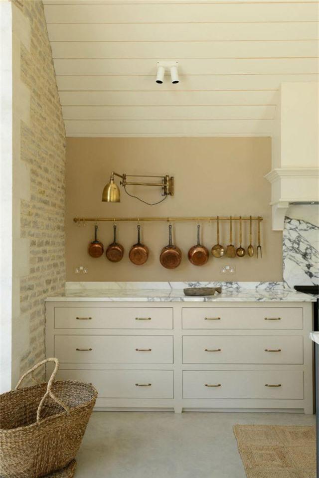 Nhà bếp kiểu Anh cổ điển được làm từ đá cẩm thạch trắng kết hợp với các đồ nội thất sáng màu cùng vật dụng mạ đồng đem lại cảm giác sang trọng.