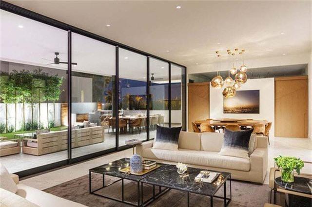 Phòng khách với nội thất trắng ngà với khung cửa sổ rộng tạo nên sự thoáng mát.