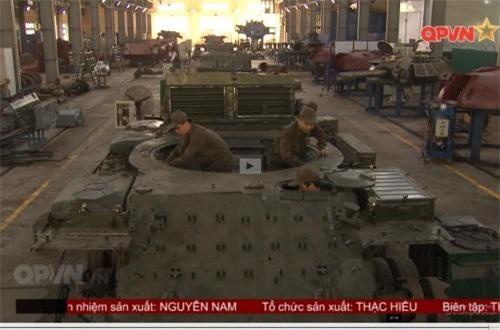 """Trong phóng sự """"Hiệu ứng từ những công trình trẻ"""" trên kênh Quốc phòng Việt Nam hôm 11/8, ngoài một số sáng kiến được giới thiệu, đoạn phim còn xuất hiện hình ảnh rất đặc biệt liên quan tới việc chúng ta đang sửa đổi khung gầm và tháp pháo xe tăng T-54. Có khả năng, đây là dây chuyền cải tiến hàng loạt các xe tăng T-54 cho lực lượng tăng – thiết giáp. Qua ảnh, có thể thấy ít nhất 4 khung gầm T-54 đang được trang bị thêm máy móc, chuẩn bị lắp thêm giáp, ngoài ra có 1 tháp pháo đã lắp đầy đủ và 3 tháp khác đang chờ tới lượt. Ảnh: QPVN"""