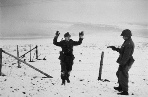 Vào giữa tháng 12/1944, trận chiến Bulge kéo dài trong 6 tuần diễn ra ở Bulge, mặt trận phía Tây. Nhiếp ảnh gia Robert Capa đã chụp được nhiều bức ảnh hiếm về trận Bulge - trận chiến vĩ đại nhất trong lịch sử quân sự Mỹ. Trong ảnh là lính Mỹ chĩa súng về phía tù nhân chiến tranh Đức.