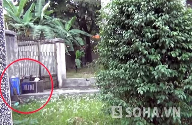 Một máy xay nước mía cùng ghế nhựa được cất gọn sau cánh cổng phụ của căn nhà