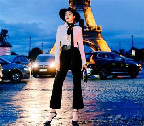 """Dự show diễn của Saint Laurent, Kỳ Duyên diện set đồ mang tông đen trắng cá tính. Giữa tiết trời 14 độ C, cô vẫn """"dũng cảm"""" diện áo sơ mi mỏng tang."""
