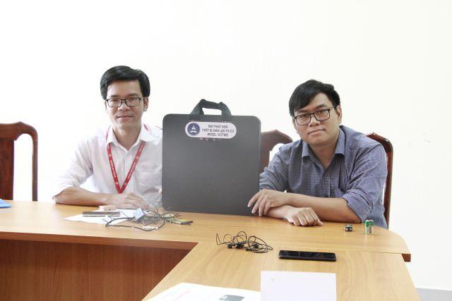 Anh Tôn Thất Trường Nam (bên phải) và thầy Trần Quốc Lâm bên cạnh chiếc máy phát hiện gian lận trong thi cử.