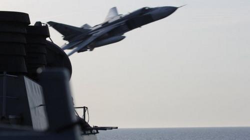 Máy bay ném bom tiền tuyến Su-24 của Nga áp sát khu trục hạm USS Donald Cook. Ảnh: TASS.